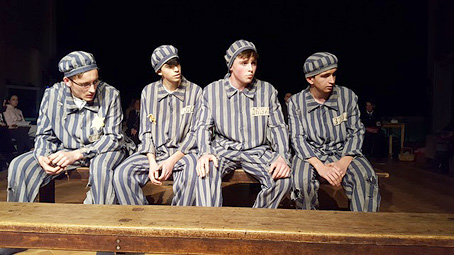 A scene showing Andreas Frohlich and 3 fellow prisoners, seated, wearing the Mauthausen concentration camp's striking prison uniform (with prominent vertical stripes, and matching cap)